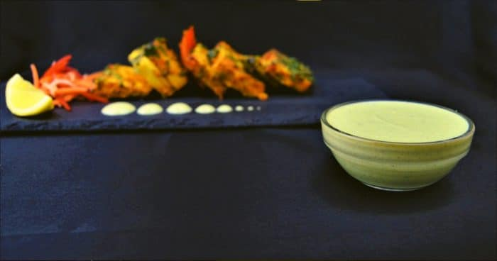 yogurt mint sauce in a bowl with paneer tikka on black plate
