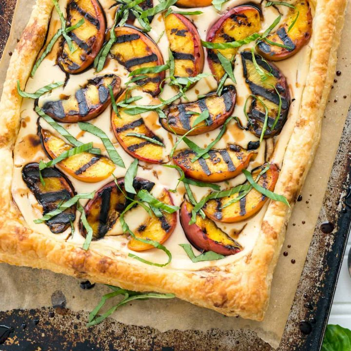 Grilled peaches and cream pastry on a baking sheet next to peaches and linen