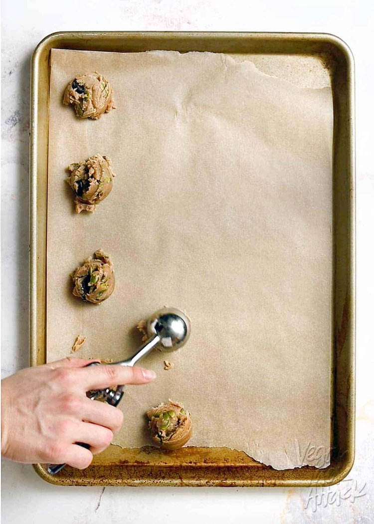Scooping vegan cookie dough onto a parchment-lined baking sheet