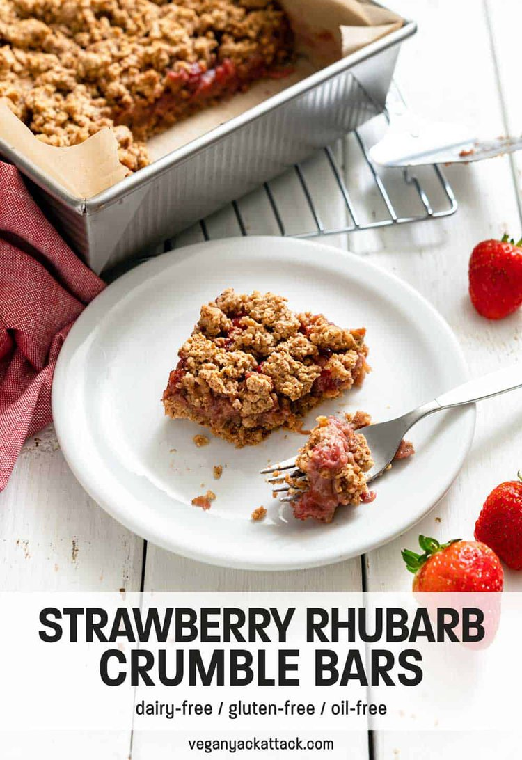 Piece of strawberry crumble bar cut out of a baking pan and bite on a fork next to it