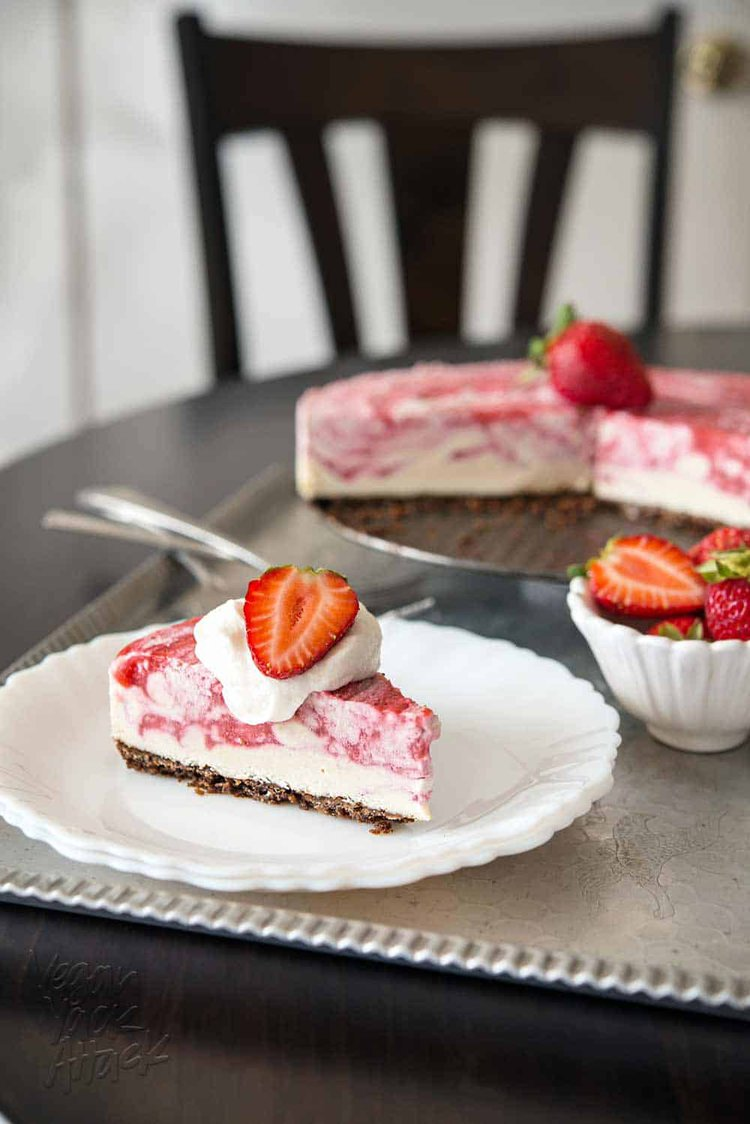 Slice of strawberry swirl cheesecake on a white plate
