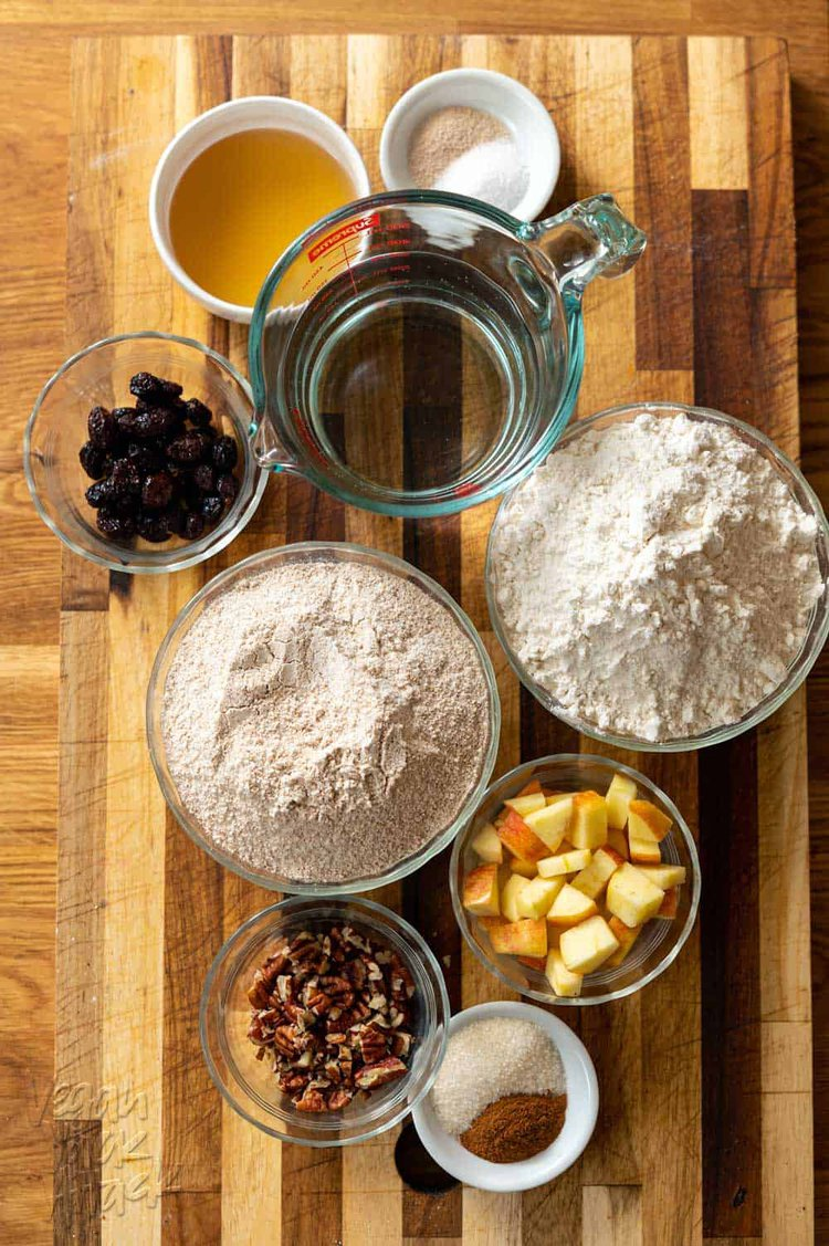 Flours, apple, pecans, craisins, water, and more, in ramekins on a cutting board