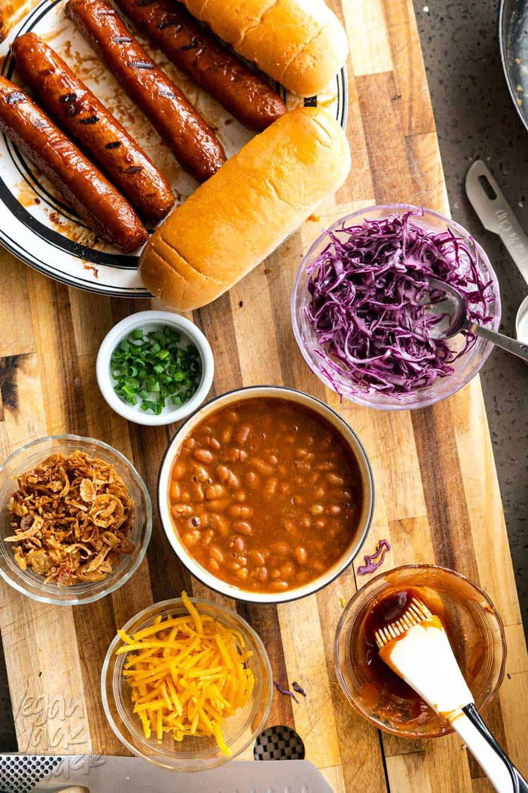 Beans, slaw, hot dogs, and other toppings on a cutting board