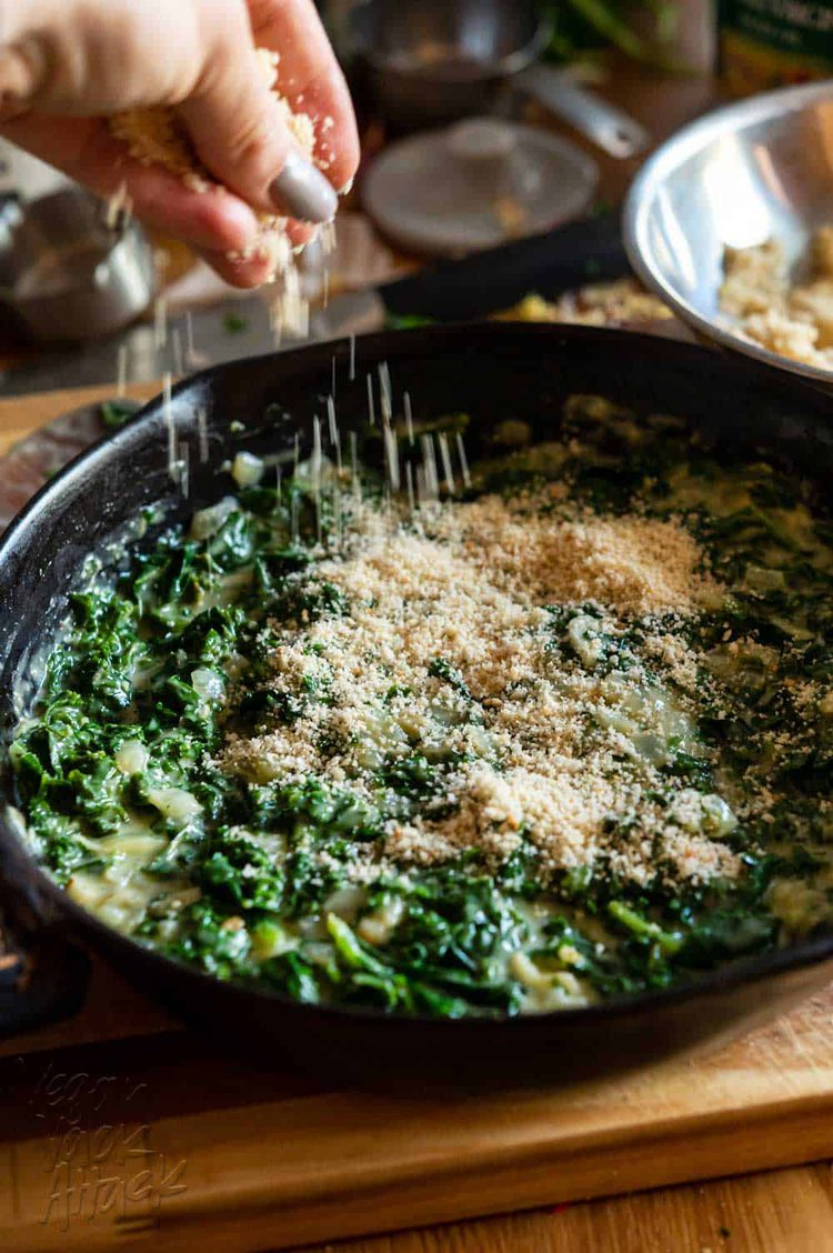 Hand sprinkling bread crumbs over creamed kale in a skillet