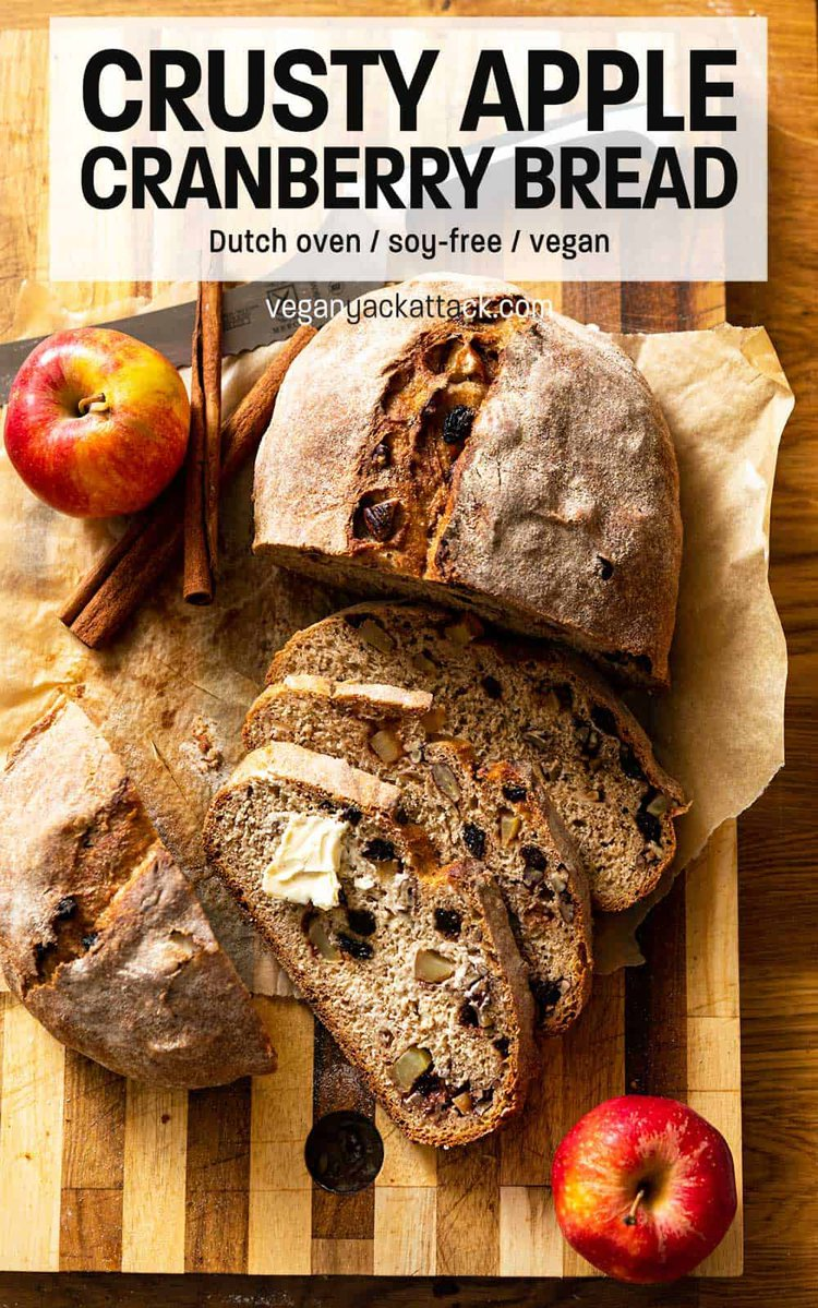 """Loaf of whole wheat bread cut partially into slices on a cutting board with text reading """"Crusty Apple Cranberry Dutch Oven Bread"""""""