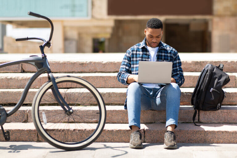 Student using his laptop on the steps next to his backpack and bicycle