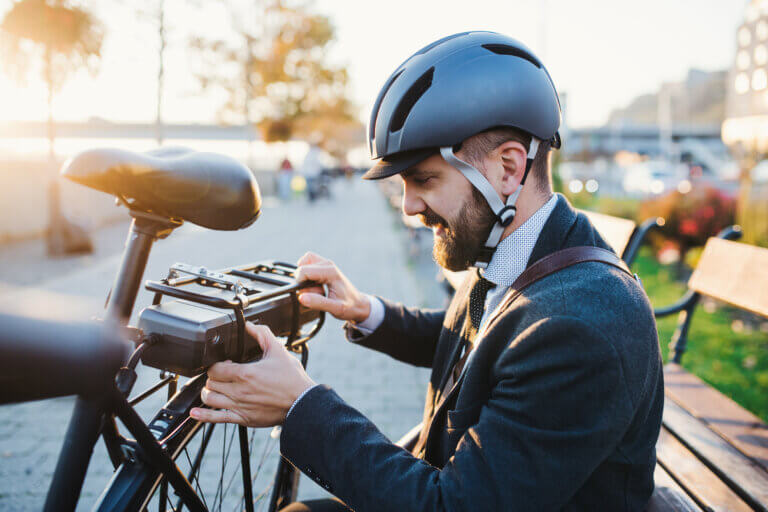 Hipster businessman commuter setting up electric bicycle when traveling home from work in city