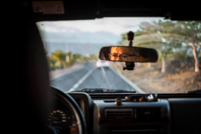 Man in the reflection of his rear view mirror while driving