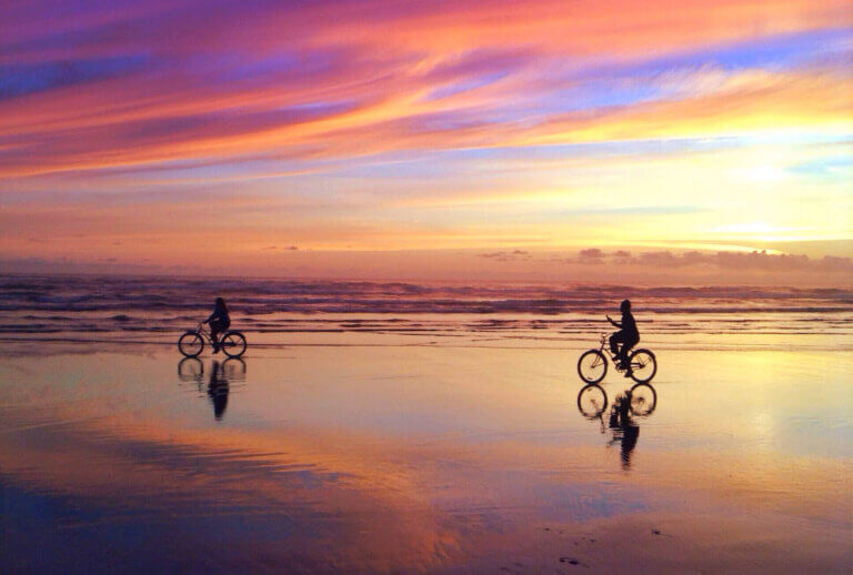 Couple riding their bicycles on the beach at sunset