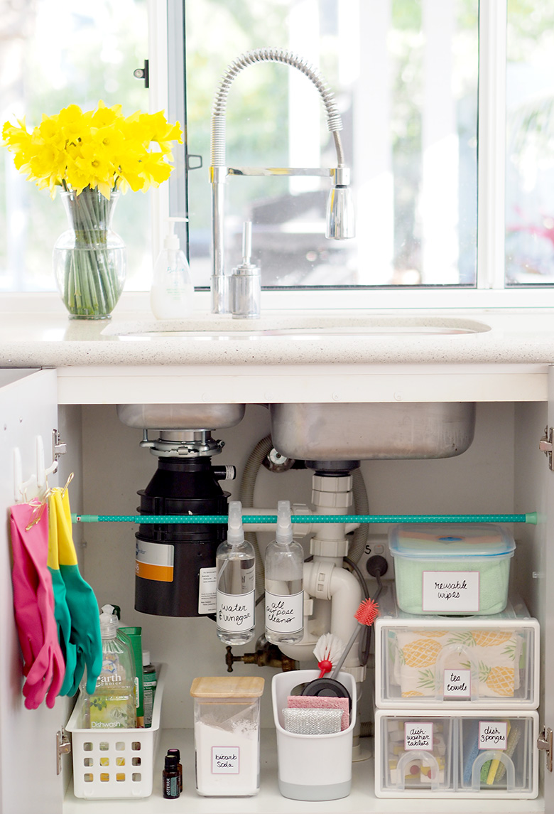 kitchen sink with view of open cabinet storing cleaning supplies