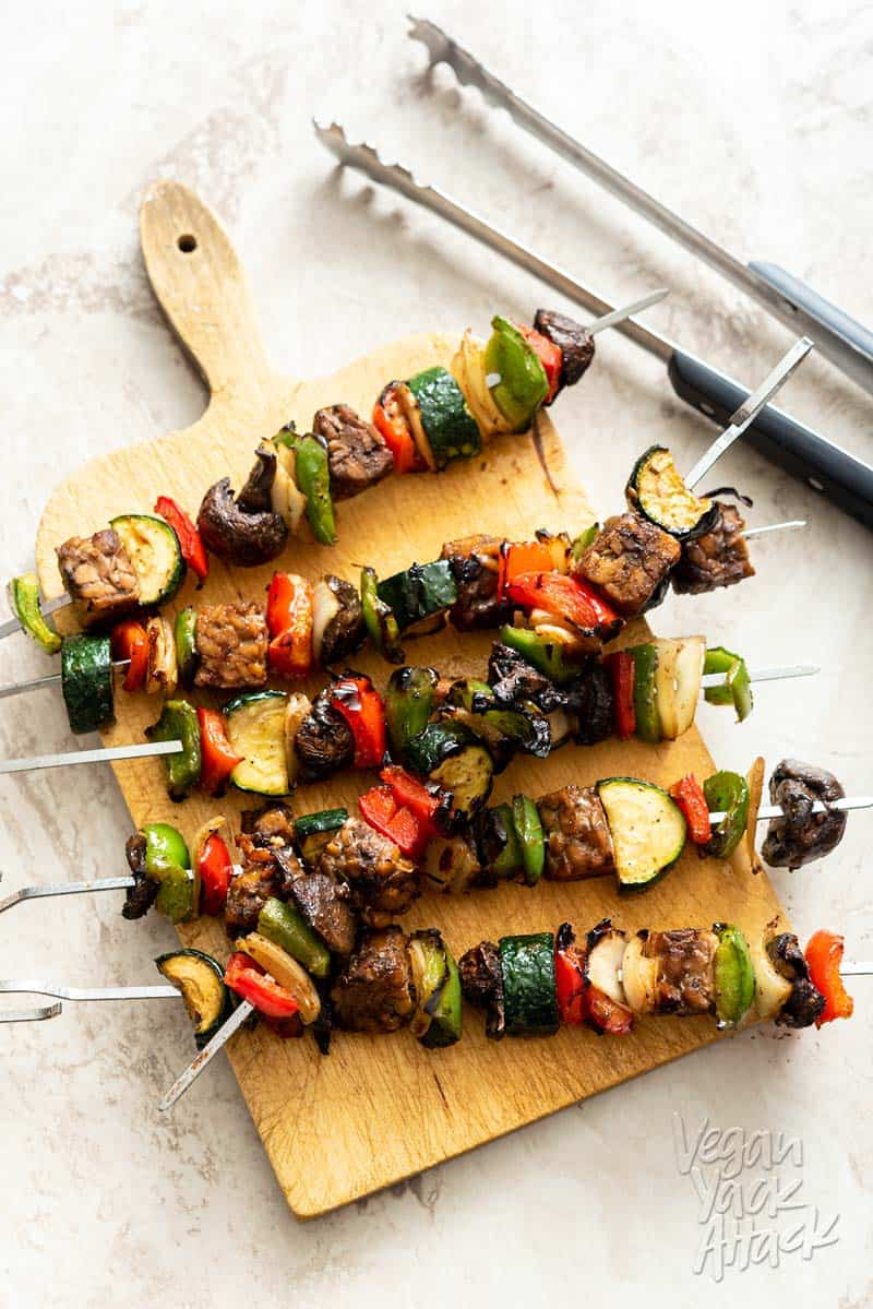 Tempeh veggie skewers stacked on a sandwich board with tongs next to them
