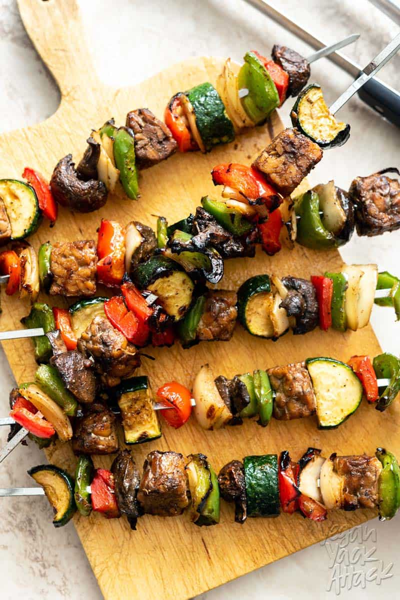 Marinated Tempeh Veggie Kabobs on a wood sandwich board