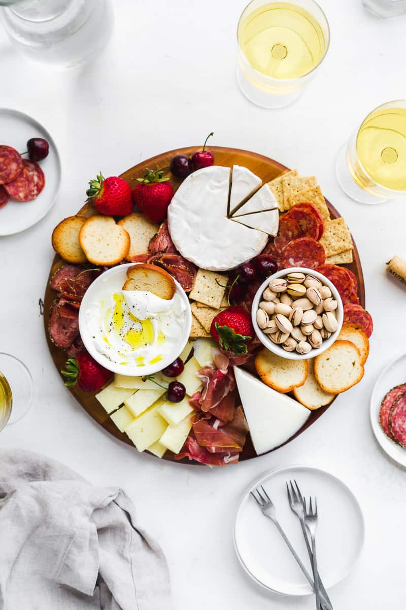 Cheese and charcuterie board on a white surface with plates.