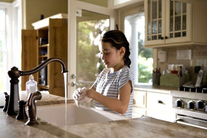 Girl washing her hands in the kitchen.