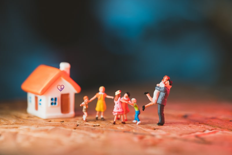 small figurines showing family celebrating as they have a new house