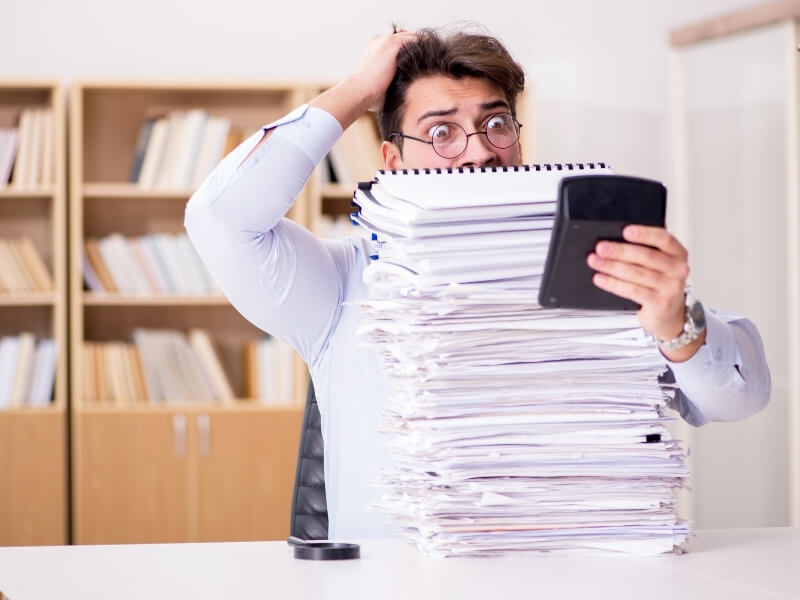 man overwhelmed with business bookkeeping after procrastinating too long