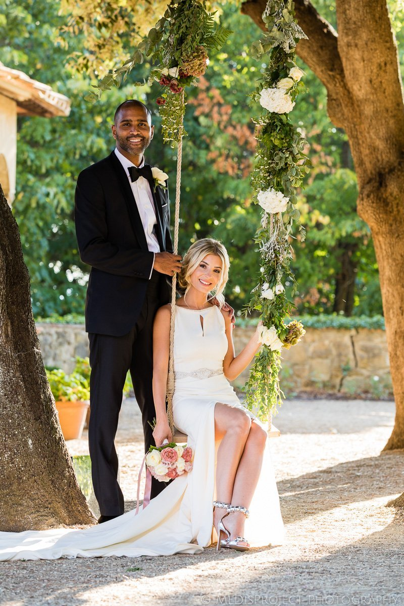 classical portrait of a beautiful happy couple with the bride sitting on a swing