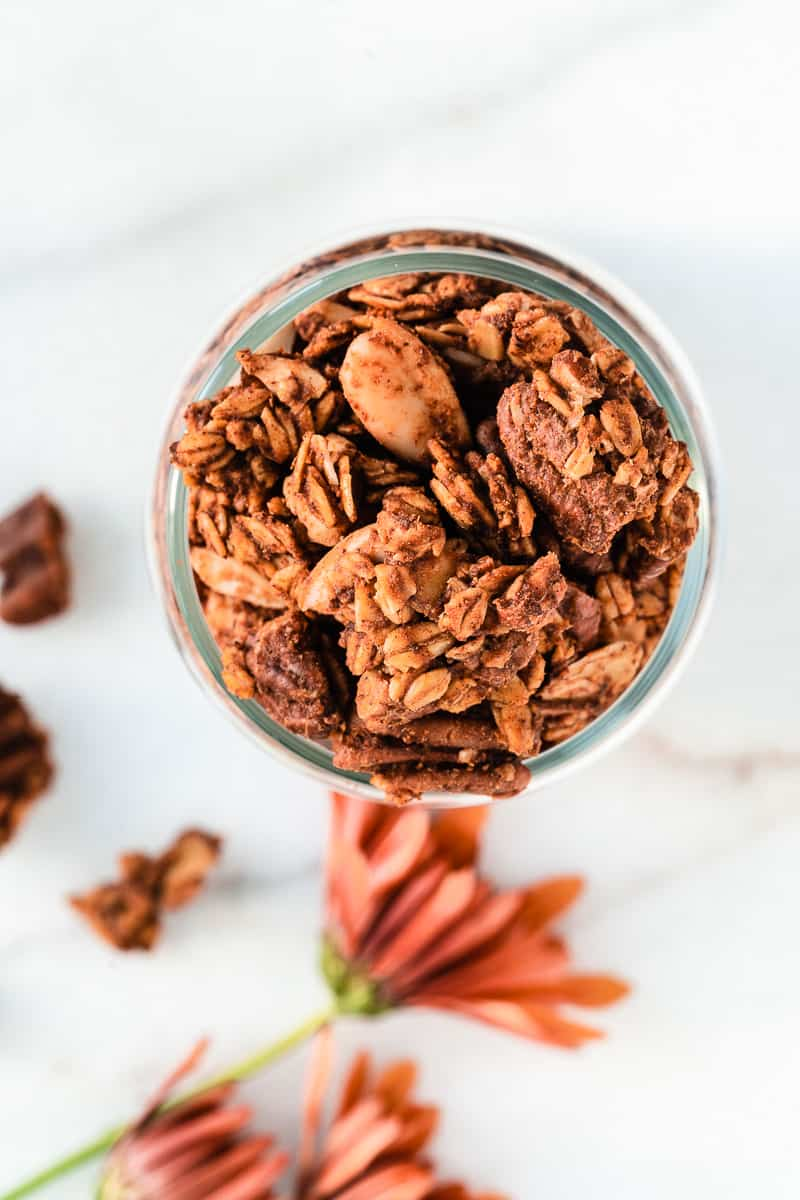 Overhead shot of pumpkin spice granola with pecans and orange flowers on surface