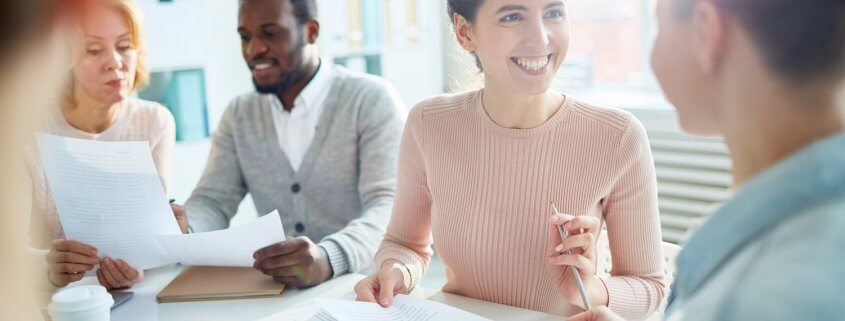 female accountant smiling at colleague during accounting firm meeting