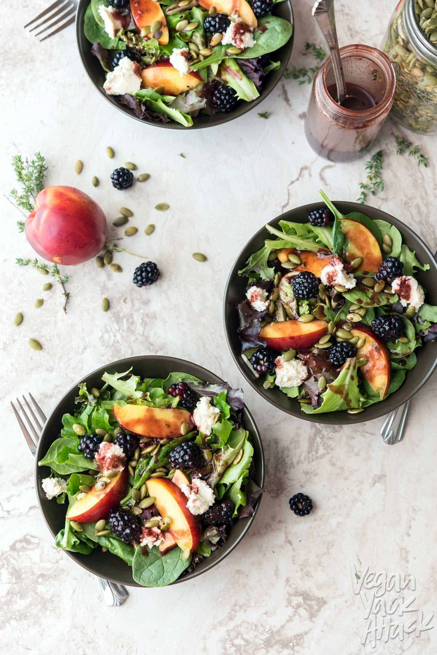 Three bowls of summery salad on a marble table top, next to seeds, a peach, and blackberries