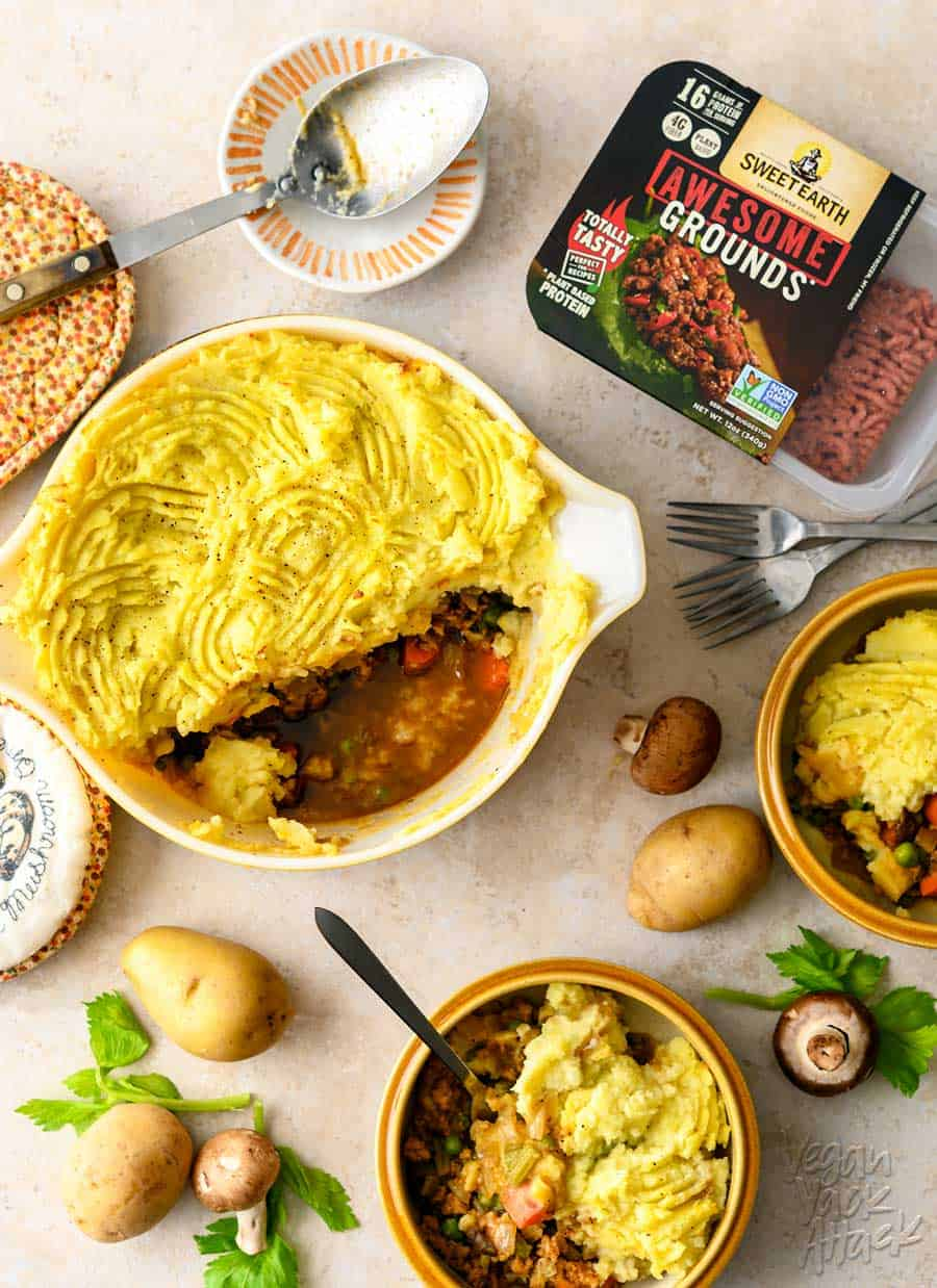One casserole dish filled with a vegan shepherd's pie, spooned into two bowls, with potatoes and mushrooms scattered around them, on a light linoleum background. There is also a container of Sweet Earth Foods Awesome Grounds in the upper right corner.