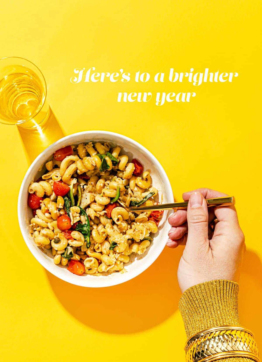 Bowl of pasta with hand holding fork, and champagne flute on a yellow background