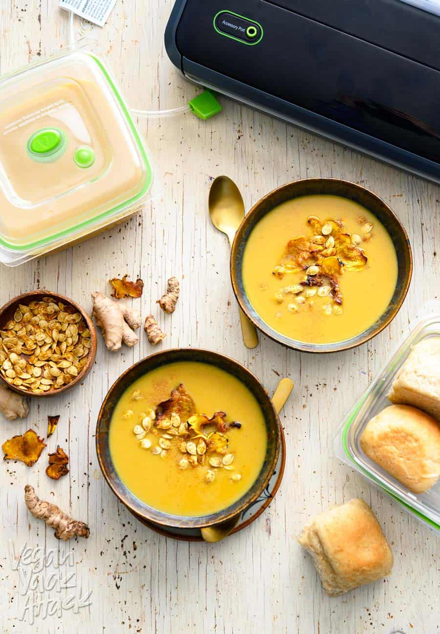 Two bowls of ginger turmeric squash soup with FoodSaver system and containers