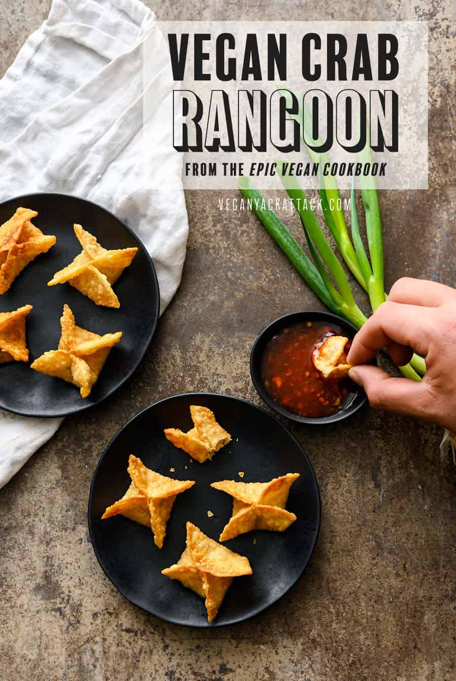 """A hand dipping vegan Crab Rangoon into sweet chili sauce, with two black plates of Crab Rangoon, on a napkin and grey background. Text on image reads """"Vegan Crab Rangoon from the Epic Vegan Cookbook"""""""