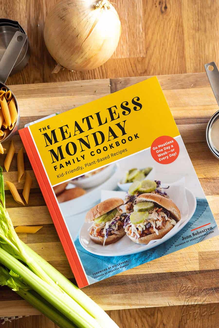 The Meatless Monday Family Cookbook on a cutting board with dried pasta, celery and onion.