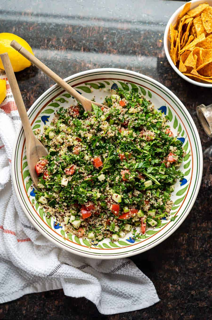 Image of kale quinoa tabbouleh salad in a large ceramic bowl, on granite countertop.