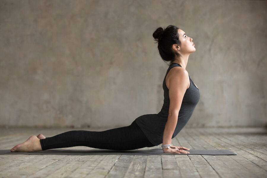 Young woman doing upward facing dog exercise - yoga poses for flexibility