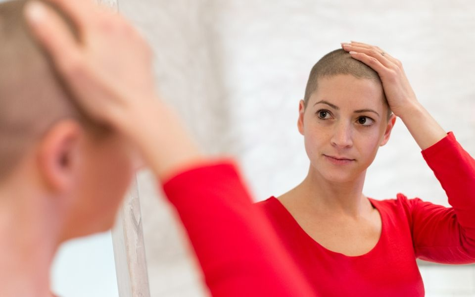 Woman with shaved head preparing for chemotherapy