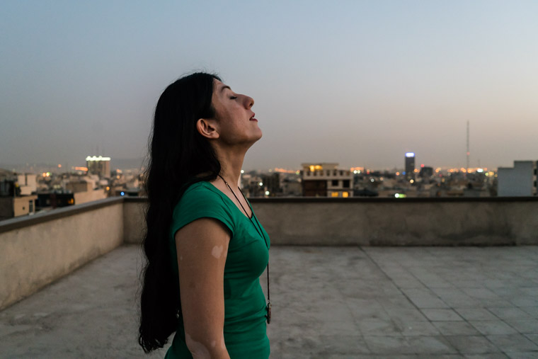 Iranian female singer Sayeh on the rooftop of her home in Tehran enjoying the sunset.