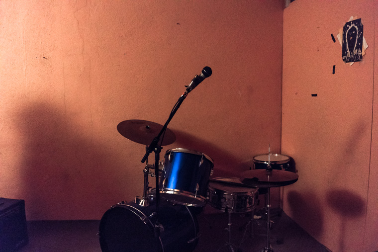 A blue drumset in front of orange walls in a basement rehearsal room in Tehran.