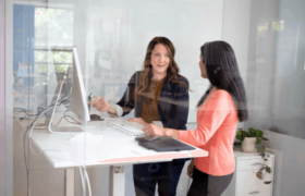 2 women talking at a standing desk. One woman points to the computer monitor.