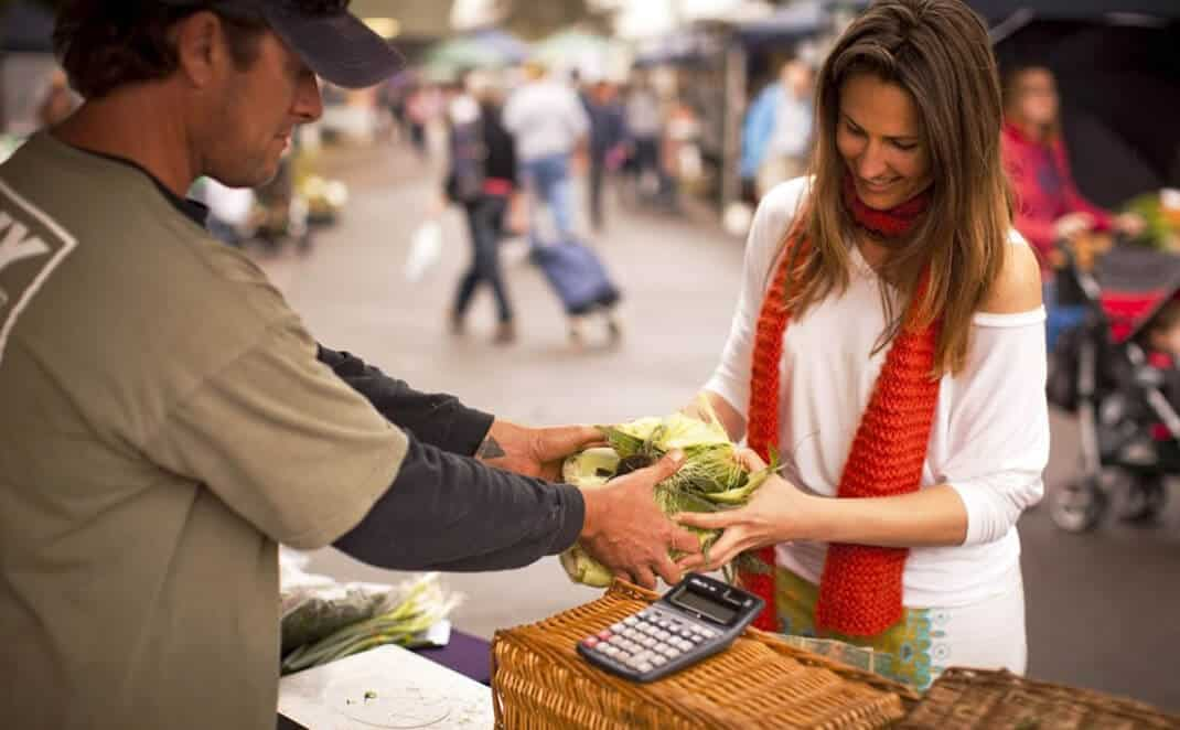 Lady buying cabbage in market