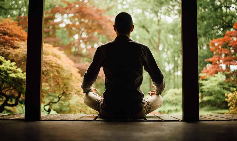 Hoe mindfulness werkt: trainer die zittend in meditatiehouding mindfulness beoefend