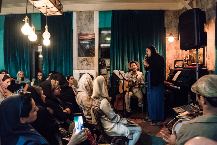 Iranian female vocalist singing in front of an audience at an open mic session in a cefe in Tehran, iran.
