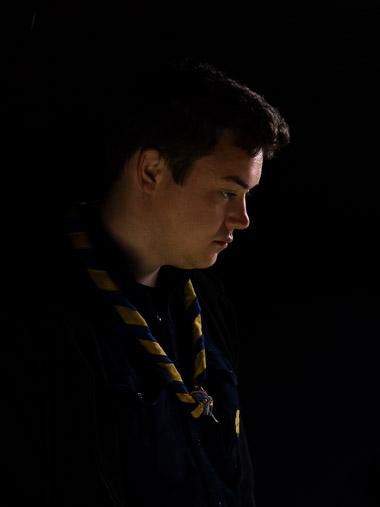 Portrait eines Pfadfinders vor dunklem Hintergrund. / Portrait of a boy scout against a dark background.