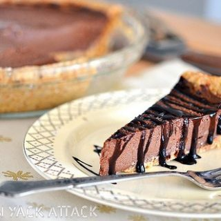 Slice of Raw Chocolate Mousse Pie with Chocolate Drizzle on a plate with fork