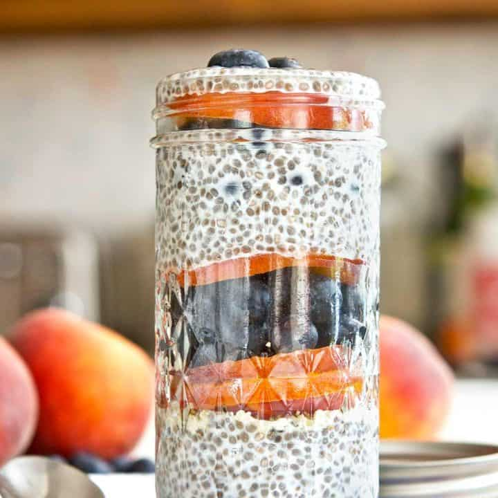 Blueberry peach chia parfait in a glass jar on a floral linen