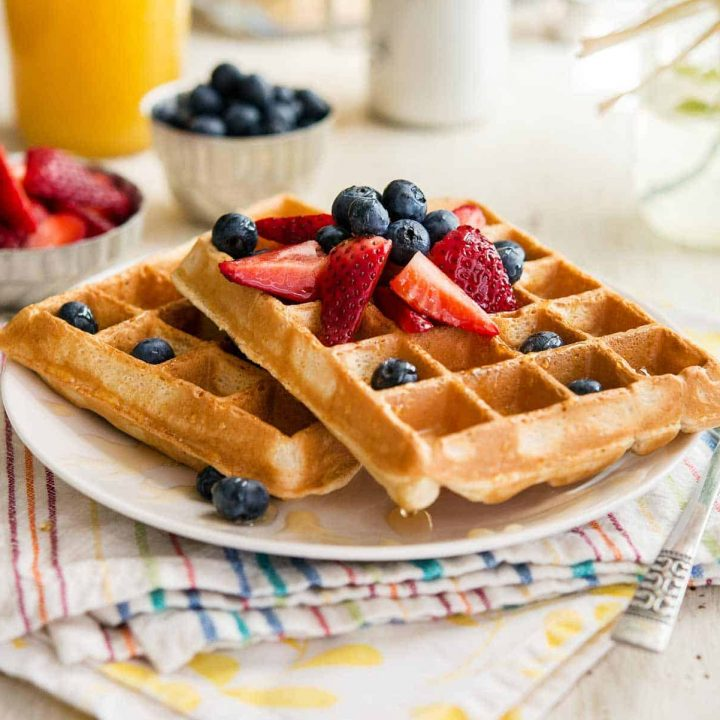 two berry pineapple belgian waffles on a white plate, topped with berries, sitting atop two colorful napkins