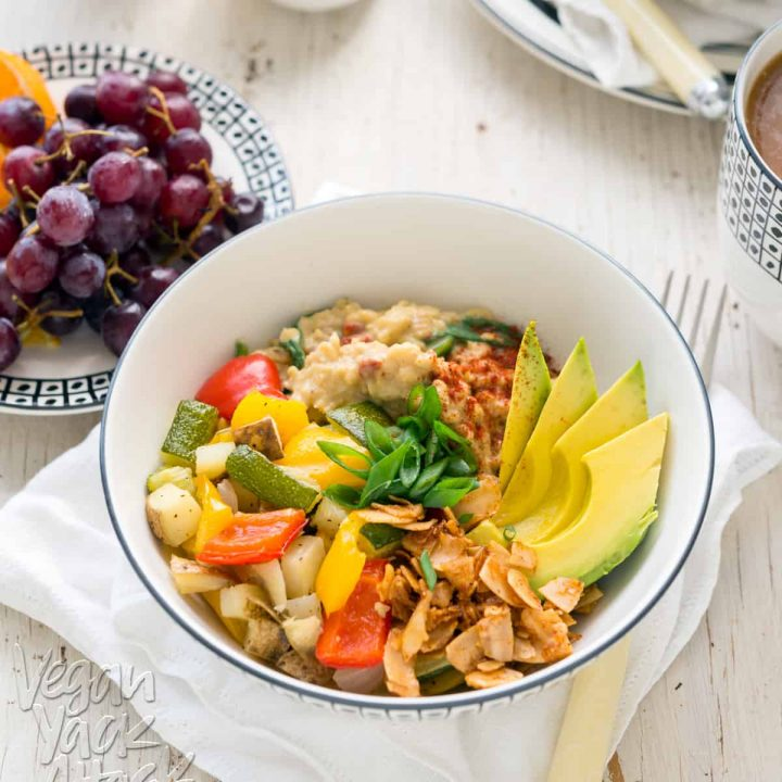 Image of bowl of savory oats with veggies, coconut bacon, and avocado, on a white table top