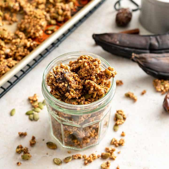 Jar of buckwheat granola next to ripe bananas and baking sheet