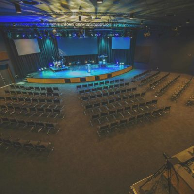 A Large Auditorium With A Stage And Seating And Blue Light's.