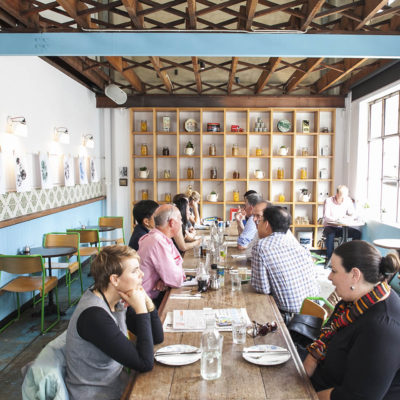 Guests seated at long wooden table in blue room with ceramic artefacts on shelving on back wall