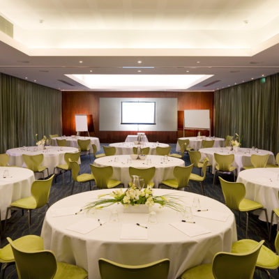 A Meeting Room With Round Tables, Green Chairs And A Tv at The Front Of The Room.