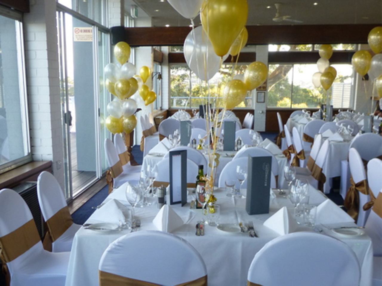 White And Yellow Theme In Tables And Chairs With Balloons Inside The Function Room