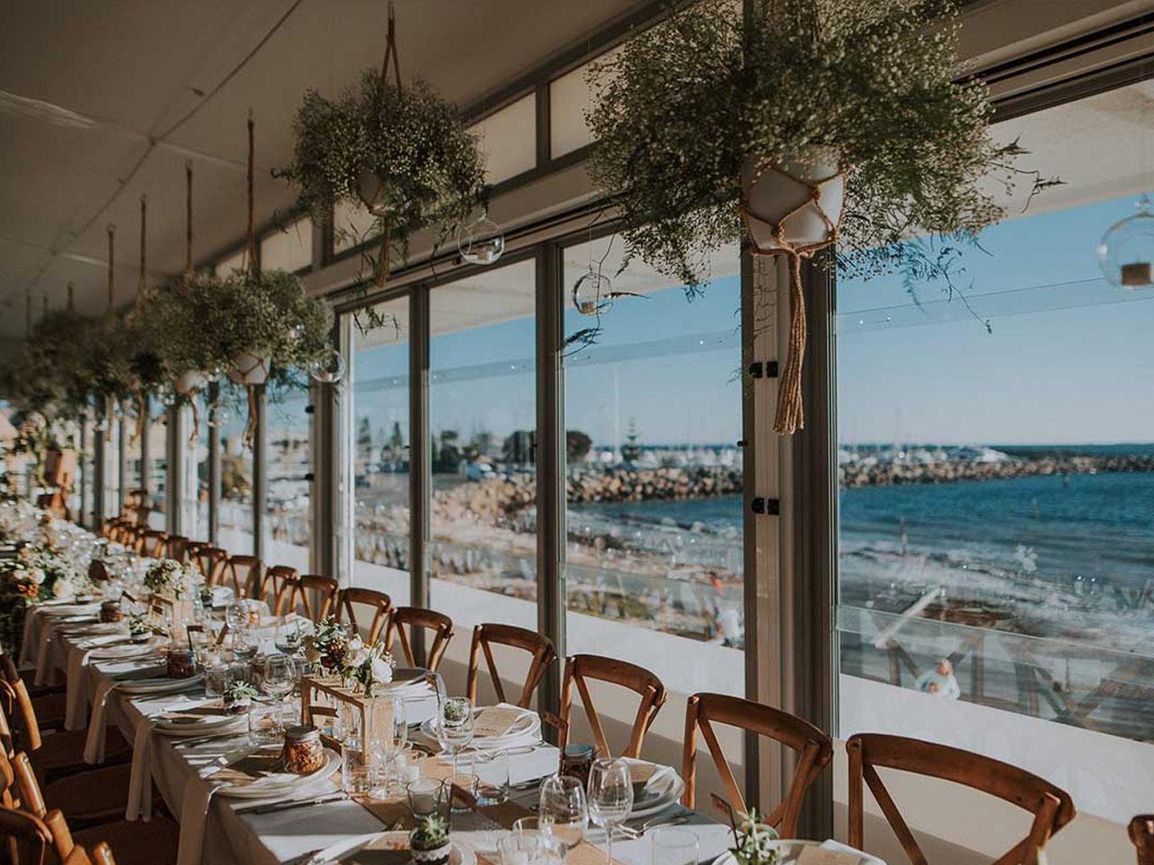 empty table setup at wedding venue overlooking beach