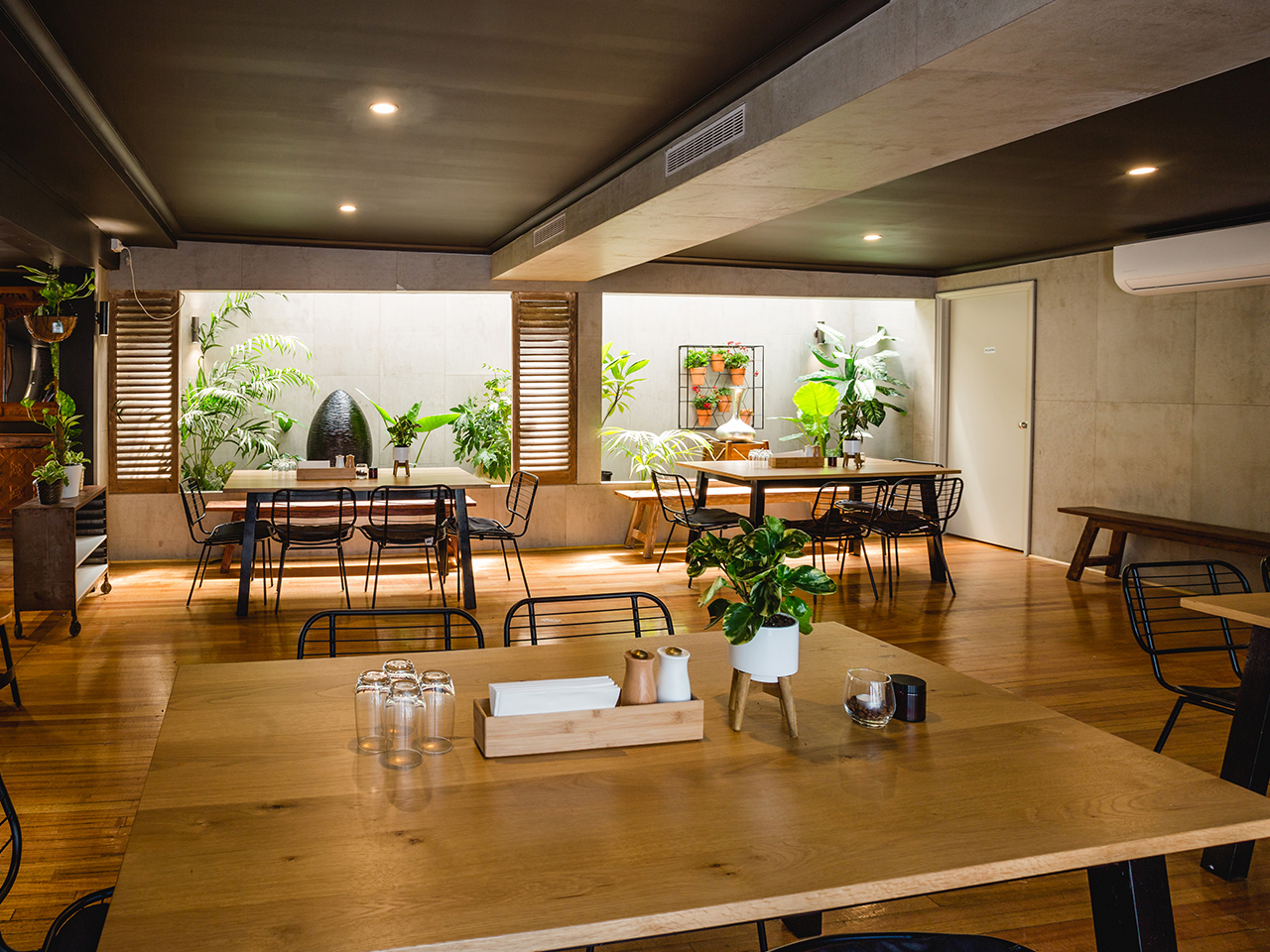 Wooden Tables With Chairs And Indoor Plants Inside The Function Room